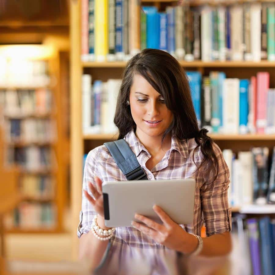 woman in library registering online for adult education class