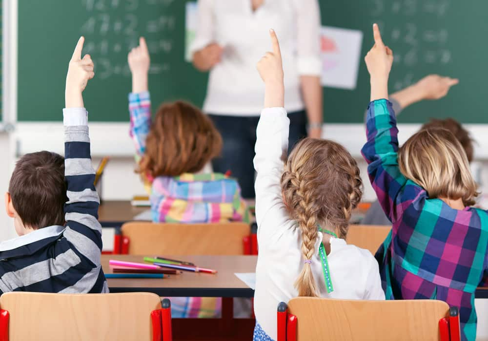 Elementary school aged children raising their hands in class to symbolize Before and After Care Online Registration
