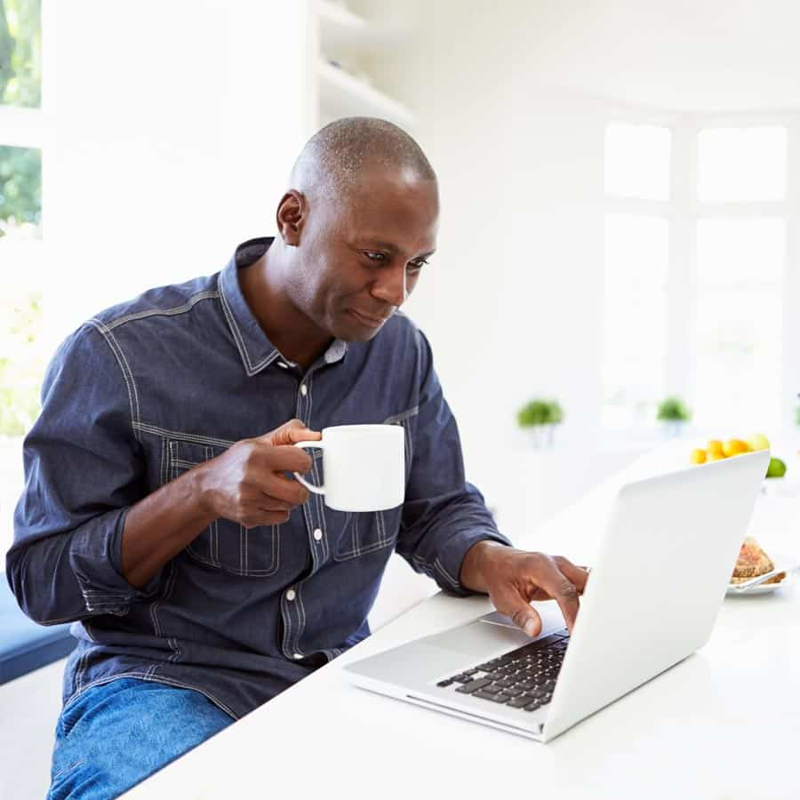 man at computer with coffee doing online registration