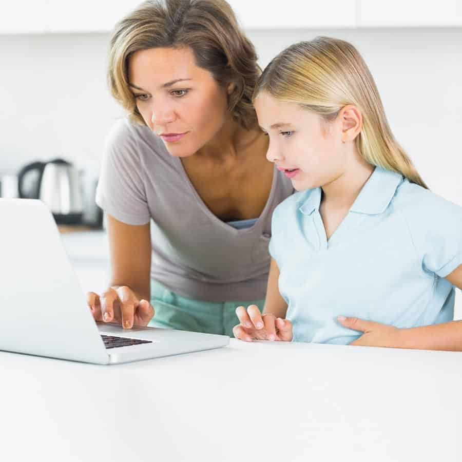 A mom with her daughter as she does online registration on her laptop for the parent teacher organization